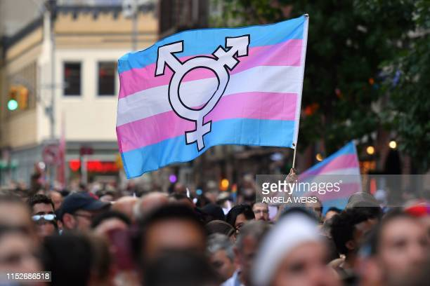 Person holds a transgender pride flag as people gather on Christopher Street outside the Stonewall Inn for a rally to mark the 50th anniversary of...