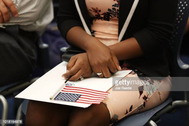 A person holds an American flag as they participate in a ceremony to become an American citizen during a US Citizenship Immigration Services...