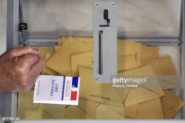 A person holds an electoral card during the first round of the French presidential election on April 23 2017 in MartresTolosane southwestern France /...