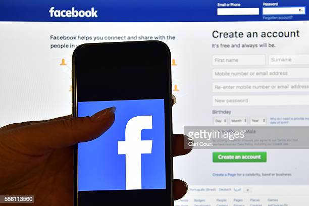 Person holds an iPhone displaying the Facebook app logo in front of a computer screen showing the facebook login page on August 3, 2016 in London,...
