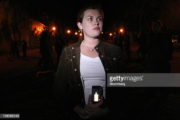 Hannah Roemhild holds an iPhone displaying the image of a candle during an iPhone vigil for Steve Jobs cofounder and former chief executive officer...