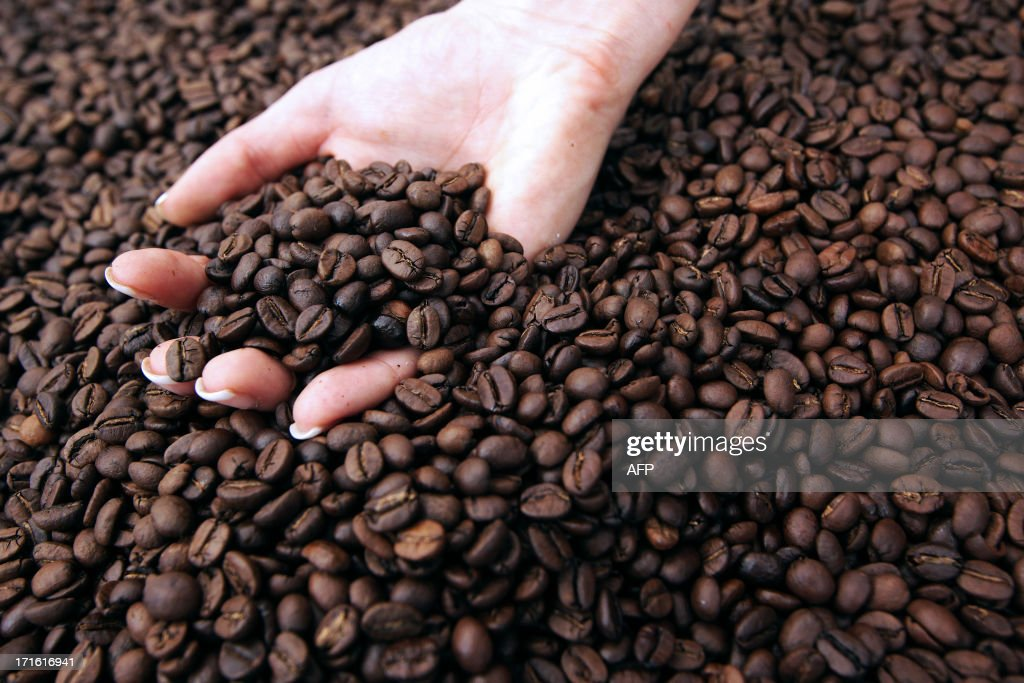 A person holds coffee beans during the exhibition 'World of coffee', on June 27, 2013, in Nice, southeastern France.