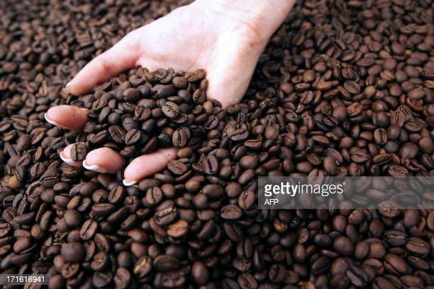 A person holds coffee beans during the exhibition 'World of coffee' on June 27 in Nice southeastern France AFP PHOTO / JEAN CHRISTOPHE MAGNENET