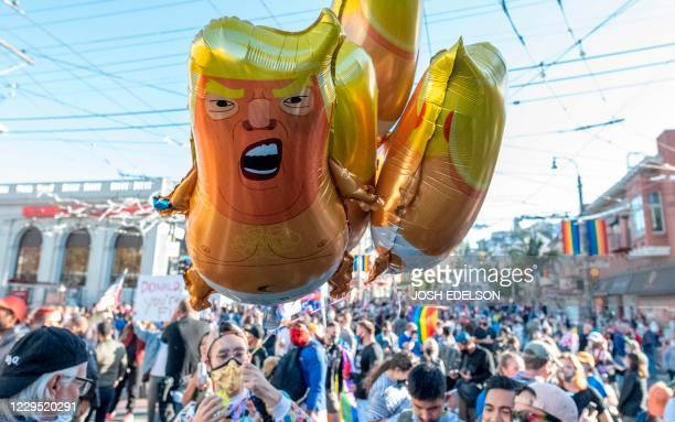 TOPSHOT A person holds Donald Trump baby balloons as people celebrate Joe Biden being elected President of the United States in the Castro district...