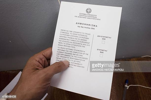 A person holds his ballot before voting during the Greek referendum on July 5 2015 in Aegina Greek voters headed to the polls today to vote in a...