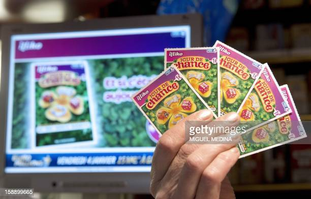 A person holds new scratchcard games called 'Jour de chance' on January 3 2013 in Paris The Française des Jeux the operator of France's national...