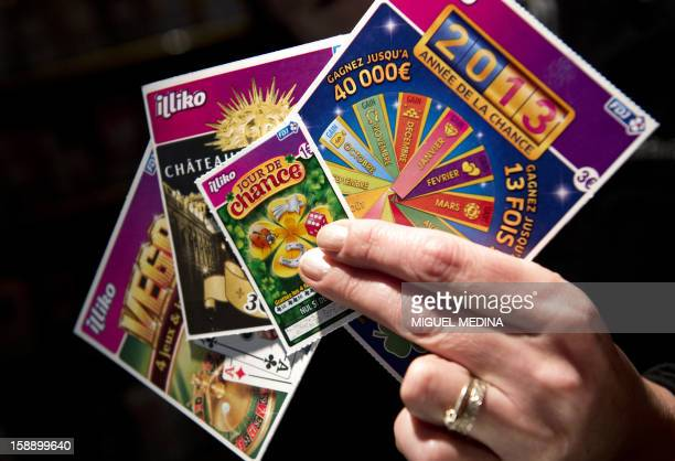 A person holds scratchcard games January 3 2013 in Paris The Française des Jeux the operator of France's national lottery games announced on January...