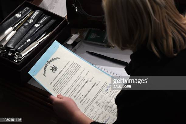 Person holds the certificate of votes from the commonwealth of Pennsylvania during a joint session of Congress after the session resumed following...