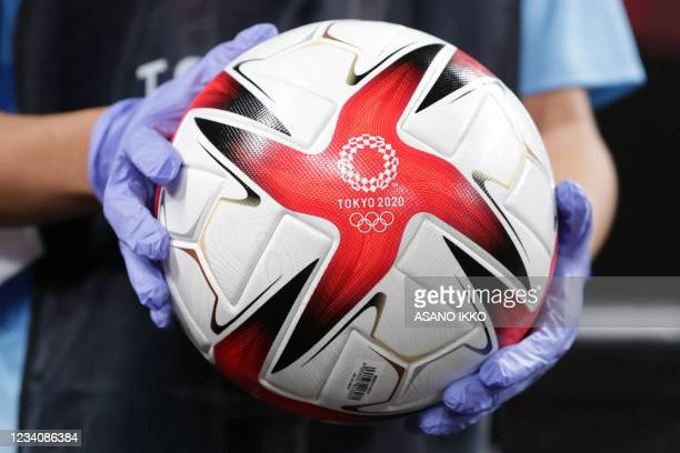 Person holds the official football before the Tokyo 2020 Olympic Games women's group E first round football match between Great Britain and Chile at...