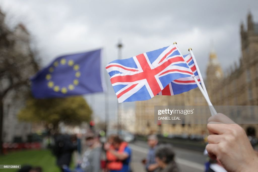 A person holds Union Flags near the Houses of Parliament in London, on March 29, 2017, after British Prime Minister Theresa May announced to the House of Commons that Article 50 of the Lisbon Treaty had been triggered, formally starting Britain's withdrawl from the European Union (EU). Britain formally launched the process for leaving the European Union on March 29, a historic move that has split the country and thrown into question the future of the European project. / AFP PHOTO / Daniel LEAL