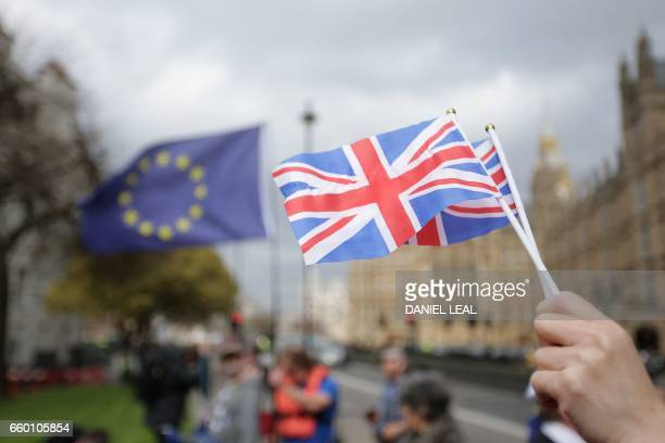 A person holds Union Flags near the Houses of Parliament in London on March 29 after British Prime Minister Theresa May announced to the House of...