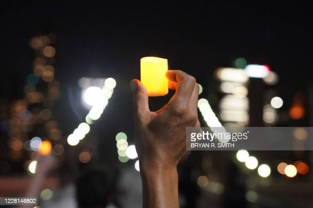"Person holds up a candle during the ""March for the Dead"" across the Brooklyn Bridge, in memory of those who have died of COVID-19 and to protest the..."