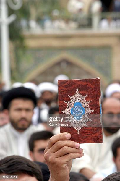 Person holds up a copy of the Quran as Iranian religious students chant during a protest at the Faizieh religious school May 18, 2005 in the clerical...