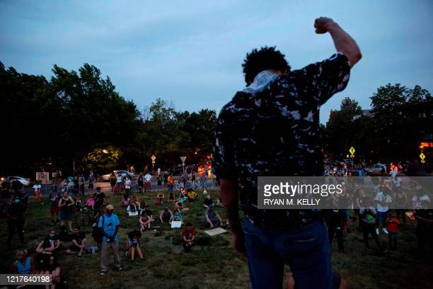TOPSHOT A person holds up a fist as people gather around the Robert E Lee statue on Monument Avenue in Richmond Virginia on June 4 amid continued...