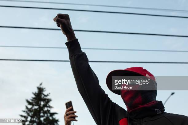 A person holds up a fist during a vigil for Manuel Ellis a black man whose March death while in Tacoma Police custody was recently found to be a...