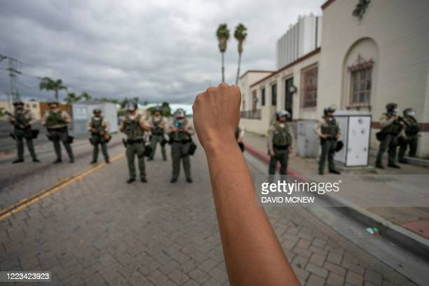 Person holds up a fist in front of a row of sheriff's deputies as relatives of Andres Guardado, who was shot and killed by a sheriff's deputy in...