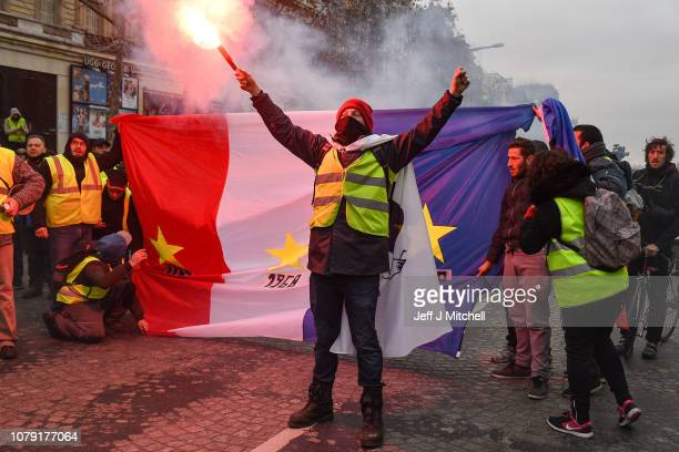 A person holds up a flare in front of the French flag as they take part in the demonstration of the yellow vests near ChampsElysees avenue on...