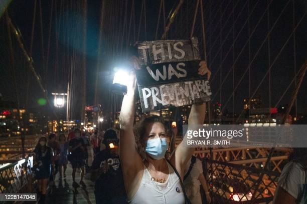 """Person holds up a placard during the """"March for the Dead"""" across the Brooklyn Bridge, in memory of those who have died of COVID-19 and to protest the..."""