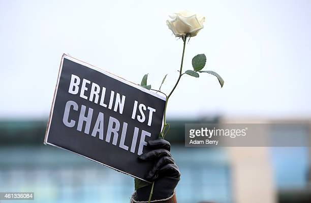 A person holds up a sign and a rose during a vigil one of several held around the world to honor the 10 journalists and two police officers murdered...