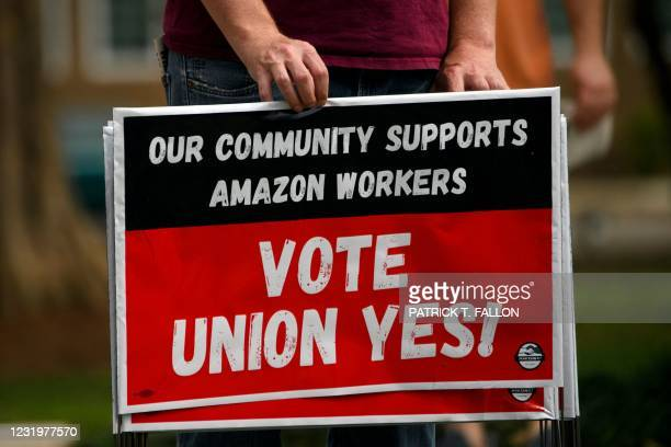 "Person holds ""Vote Union Yes!"" signs during a protest in solidarity with Black Lives Matter, Stop Asian Hate and the unionization of Amazon.com, Inc...."