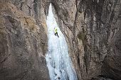 Person ice climbing on steep frozen cascade