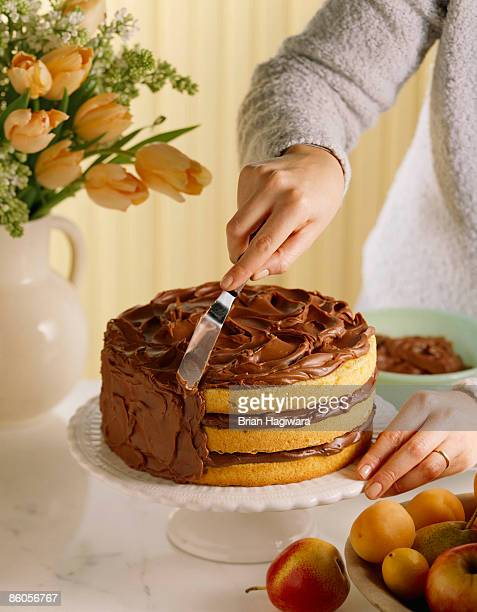 person icing layer cake - icing stock pictures, royalty-free photos & images