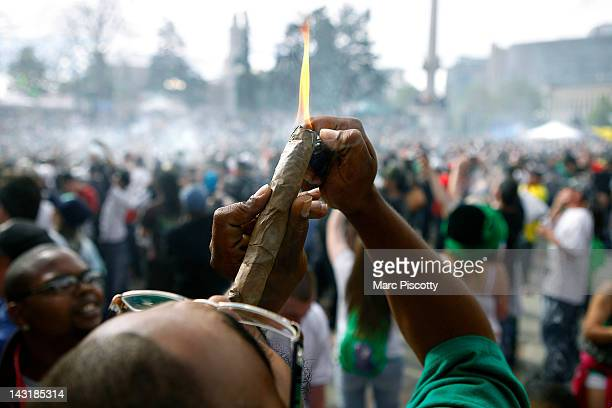 A person identifying himself as Jermagisty Tha King of Denver lights up a 28 ounce blunt at exactly 420 pm as thousands gathered to celebrate the...