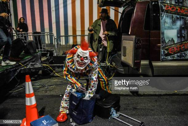 A person in a clown costume prepares to participate in the annual Village Halloween parade on Sixth Avenue on October 31 2018 in New York City