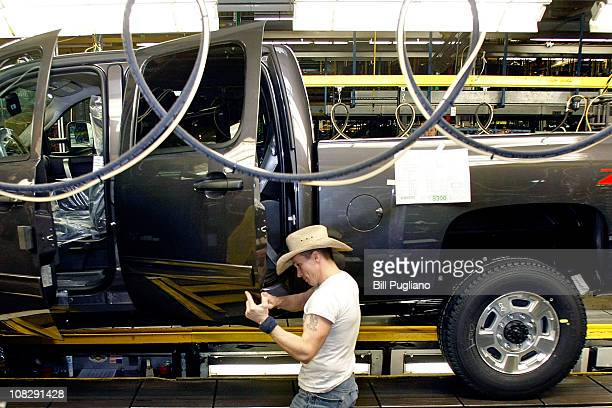 A person in a cowboy hat works on building a Chevy pickup truck on the assembly line of the General Motors Flint Assembly Plant January 24 2011 in...