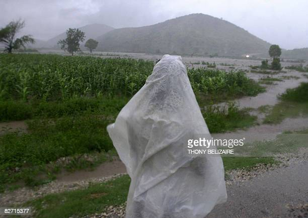 A person in a makeshift rain jacket surveys a flooded landscape September 2 2008 near Gonaives 171 km from PortauPrince in the wake of Tropical storm...