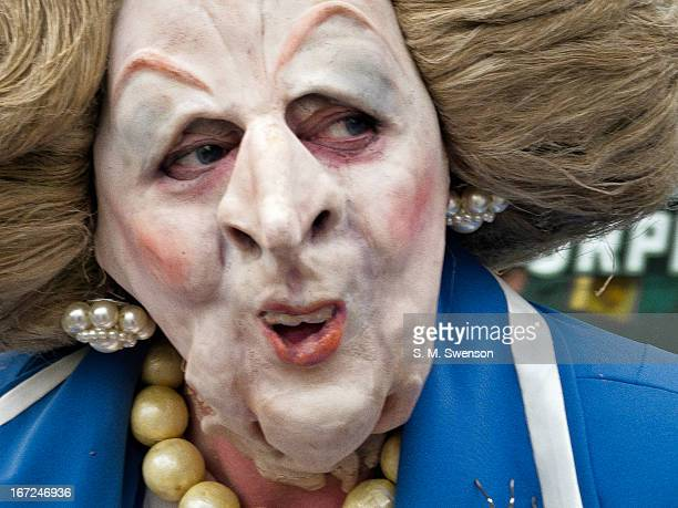 Person in a Margaret Thatcher satire mask with her trademark blue power suit, pearl necklace and earrings. It's a close-up of the face. Taken at an...