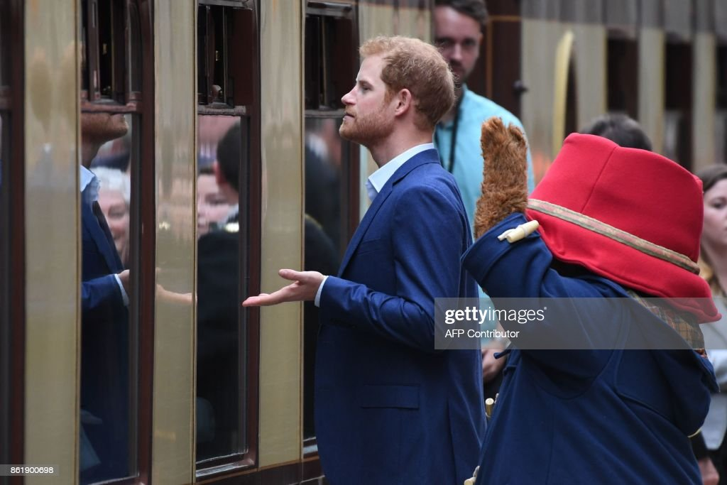 A person in a Paddington Bear outfit and Britain's Prince Harry (C) look through the windows of a Pullman train as they attend a charities forum event at Paddington train station in London on October 16, 2017. The Duke and Duchess of Cambridge and Prince Harry joined children from the charities they support on board Belmond British Pullman train at Paddington Station. The event was hosted by STUDIOCANAL, with support from BAFTA through its BAFTA Kids programme, and before embarking Their Royal Highnesses met the cast and crew from the forthcoming film Paddington 2. / AFP PHOTO / Chris J Ratcliffe