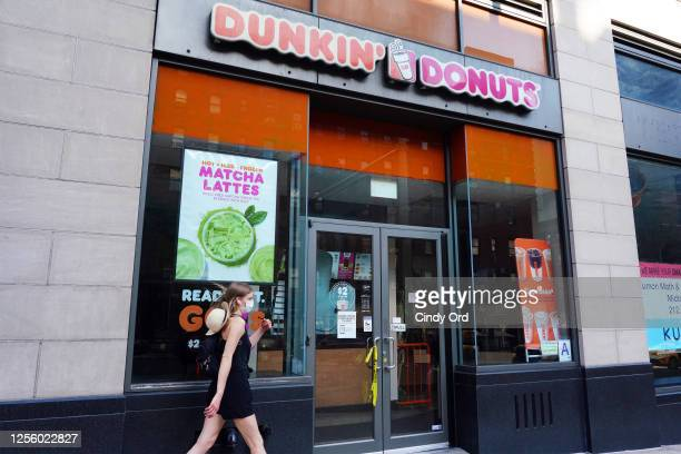 Person in a protective mask walks by a temporarily closed Dunkin' Donuts as New York City moves into Phase 3 of re-opening following restrictions...