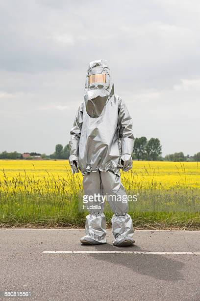 A person in a radiation protective suit standing in front of an oilseed rape field