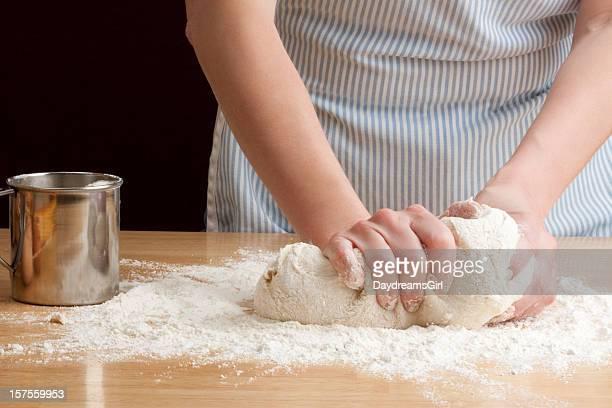 Person in apron kneading dough to make bread
