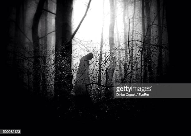 Person in bat costume in spooky forest
