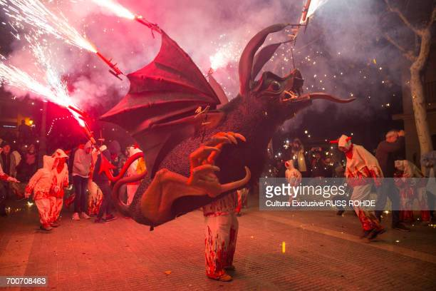 Person in bat costume parading at dimonis fiesta at night, Majorca, Spain