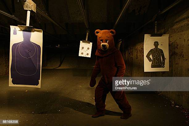 Person in bear costume at a shooting range