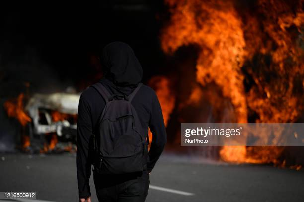 A person in black clouting looks on as police vehicles burn as protestors clash with police near City Hall in Philadelphia PA on May 30 2020 Cities...