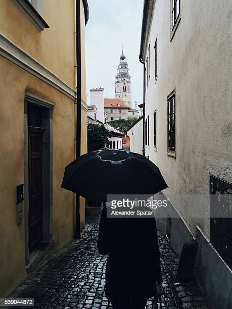 person in black holding black umbrella looking at the castle tower in the old town of cesky krumlov, south bohemia, czech republic - cesky krumlov castle stock photos and pictures