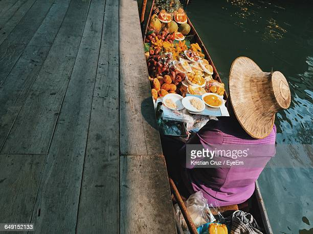 person in boat with fruits at damnoen saduak floating market - floating market stock pictures, royalty-free photos & images