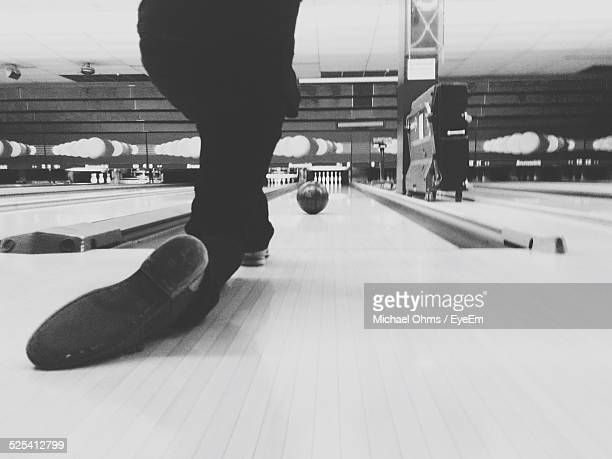 Person In Bowling Alley Rolling Bowling Ball