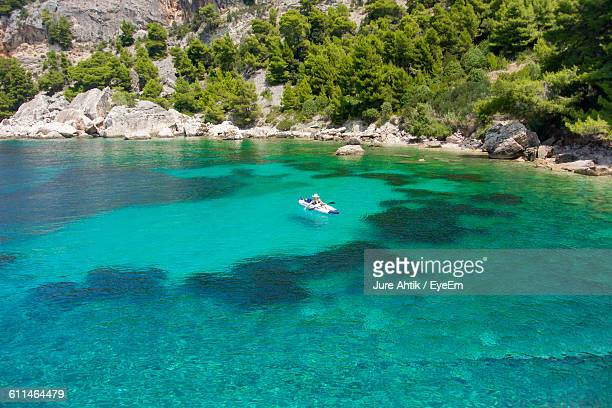 person in canoe moving on river against mountains - hvar stock photos and pictures