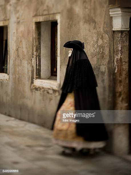 a person in carnival costume, a woman in a black cloak and dress with petticoats, wearing a white face mask and tricorn hat.  - tricornered hat stock photos and pictures