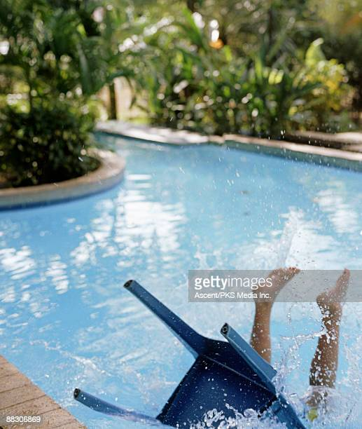 person in chair falling into swimming pool - 人工建造物 ストックフォトと画像
