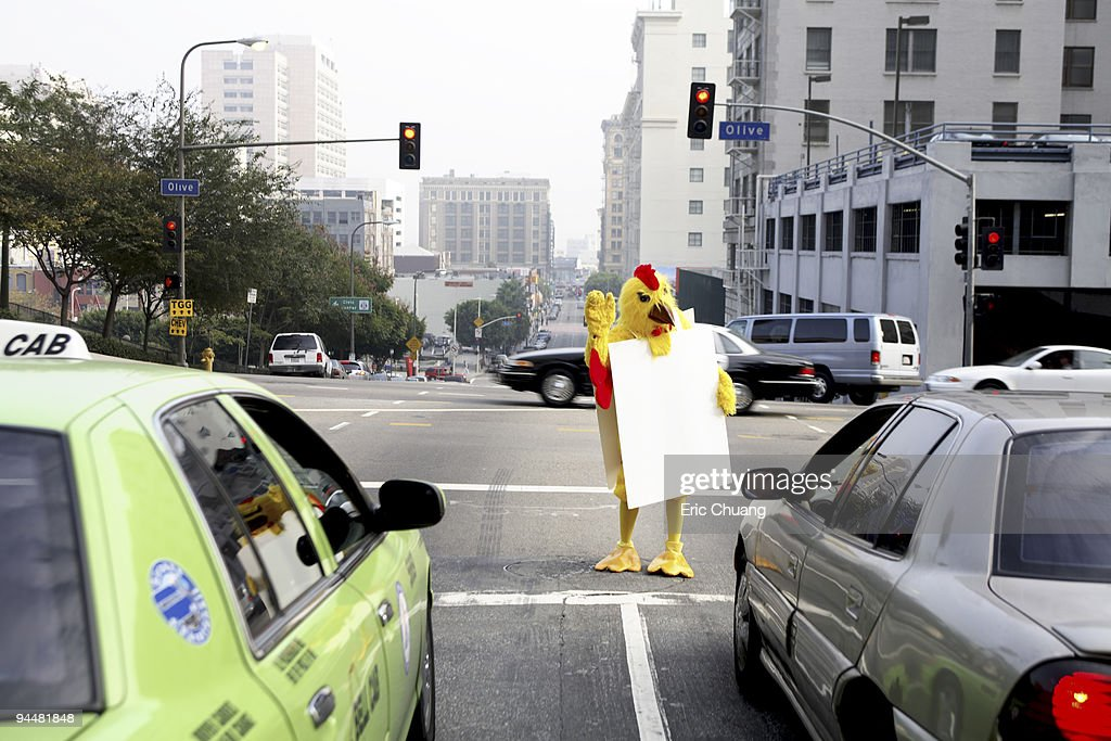 Person in chicken costume at crosswalk : Stock Photo