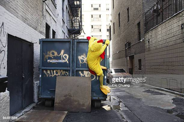 Person in chicken costume climbing up garbage dumpster