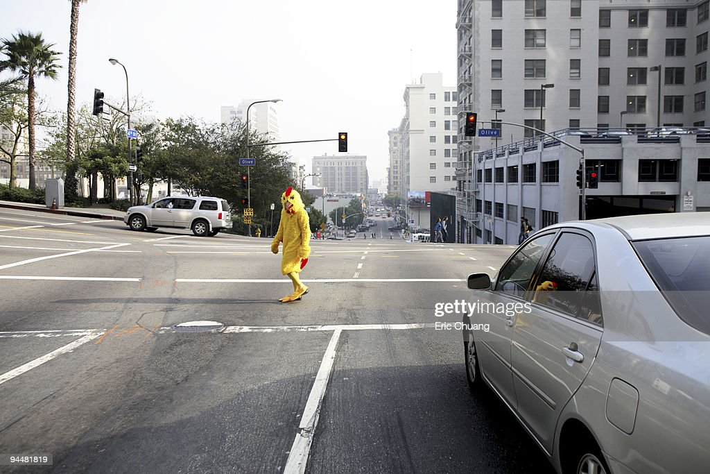 Person in chicken costume crossing the street : Stock Photo