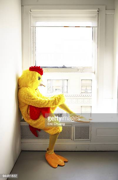 Person in chicken costume looking out window