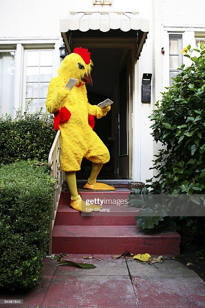 Person in chicken costume reading mail : Stock Photo